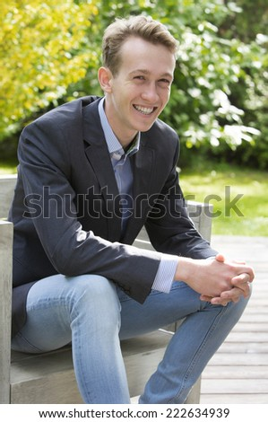 blond young man in jacket and jeans is sitting and smiling
