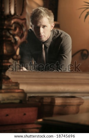 blond young man looking at himself in a mirror - stock photo
