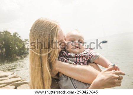 blond young Mother embracing and kissing her child against summer pine forest and sky with clouds Cute caucasian young woman stand on stoned beach near fresh water in sea  - stock photo