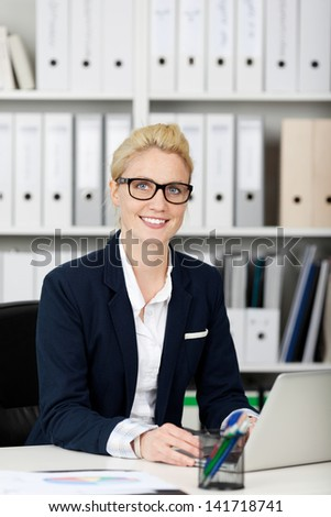 Blond young smiling female executive in office - stock photo