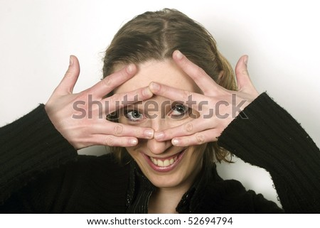 Blond young woman covering face with her fingers and peeking thorough them.