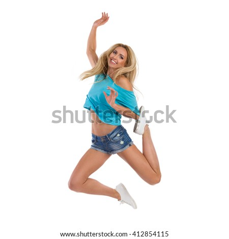 Blond young woman in jeans shorts, turquoise top and white sneakers jumping with arm raised and smiling. Full length studio shot isolated on white.