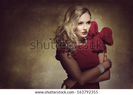 blond young woman in red dress and creative hair style , looking on one side. she has a big bow - stock photo