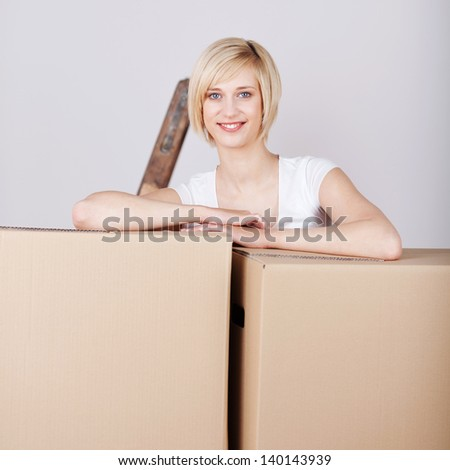 blond young woman leaning on cardboard boxes