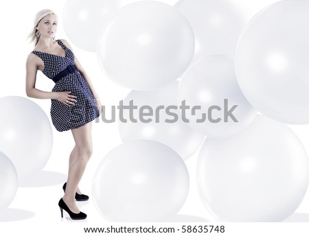blond young woman wearing blue polka dot dress jewellery and taking pose - stock photo