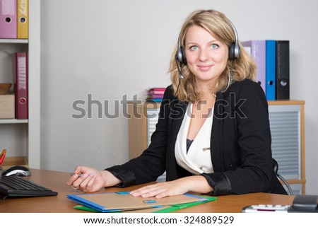 Blond young woman working in a call center - stock photo