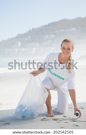 Blonde activist picking up trash on the beach on a sunny day - stock photo