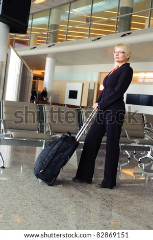 blonde adult businesswoman in black suit with luggage waiting for the departure of the plane in waiting room