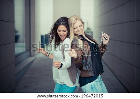 blonde and brunette beautiful stylish young women in the city - stock photo