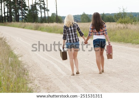 Blonde and brunette friends on country road back view - stock photo