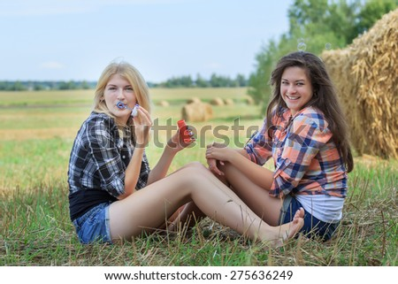 Blonde and brunette girls are making soap bubbles in ranch field - stock photo