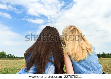 Blonde and brunette girls embracing and looking at the sky - stock photo
