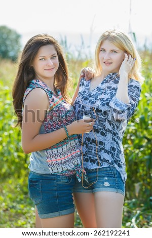 Blonde and brunette girls sharing headphones fwith each other - stock photo