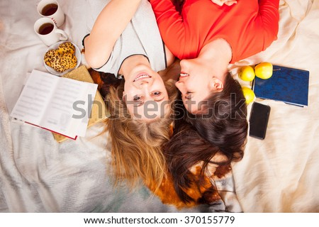 blonde and brunette lying on the couch and talking - stock photo