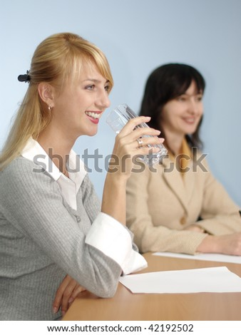 Blonde and brunette women on the meeting in the office - stock photo