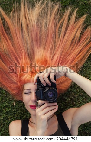 blonde and pink haired young woman laying on the green grass - stock photo