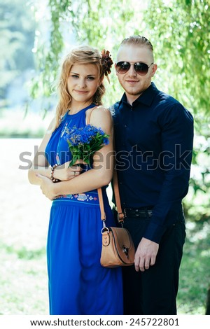 Blonde attractive couple standing against natural scenery. Blue dress with ethnic motives. Smiling girl. Stylish man in classic dark outfit wearing sunglasses. Cornflowers. - stock photo