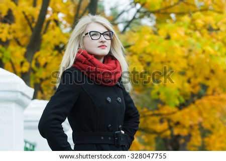 Blonde attractive young woman in black and white cat eye glasses is looking away at autumn yellow trees background - stock photo