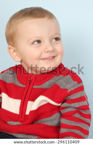 Blonde baby boy against a blue background - stock photo