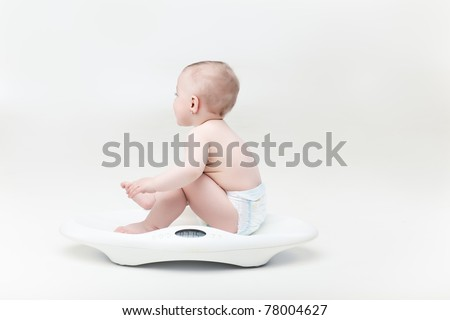 blonde baby girl sitting on baby scale