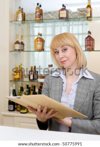 blonde barmaid at bar with wine list - stock photo