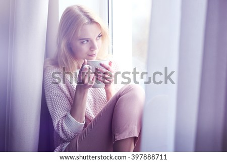 Blonde beautiful  girl sitting by the window with cup of tea or coffee in her hands - stock photo