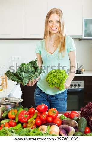 Blonde beautiful housewife cooking with fresh vegetables at home   - stock photo