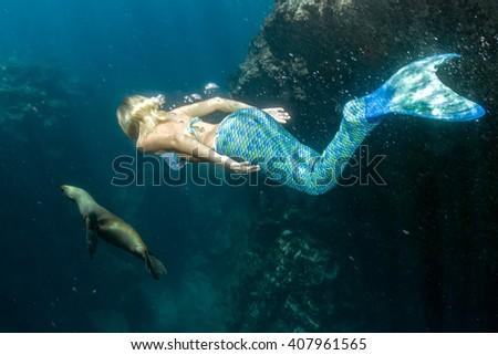 Blonde beautiful Siren Mermaid while diving underwater in the deep blue sea - stock photo