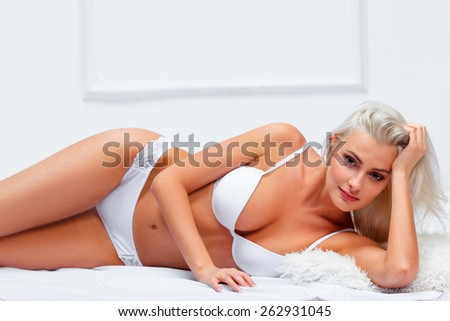 blonde beautiful womanwearing white lingerie  lying on bed  - stock photo
