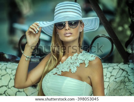 Blonde beautiful young woman with long hair posing outdoor, wearing sunglasses. Summer style. - stock photo