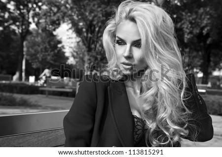Blonde beauty posing on bench - stock photo