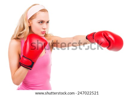 Blonde boxing. Concentrated blond hair woman in pink shirt and boxing gloves boxing while standing isolated on white background - stock photo