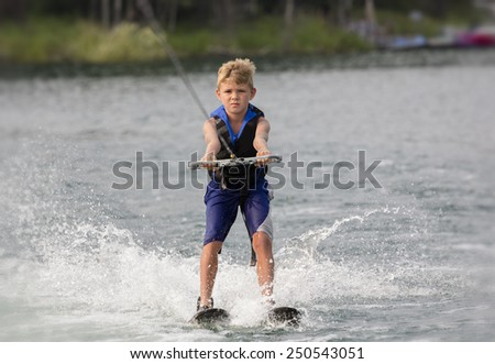 Blonde Boy learning to waterski on a lake - stock photo