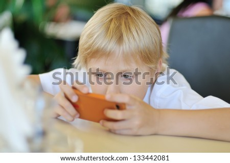 blonde boy playing phone at home - stock photo