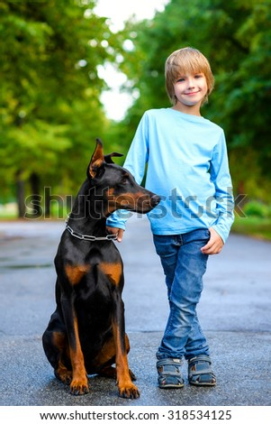 blonde boy posing with the dog or doberman in summer park - stock photo