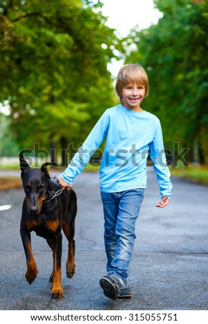 blonde boy walking with the dog or doberman in summer park - stock photo