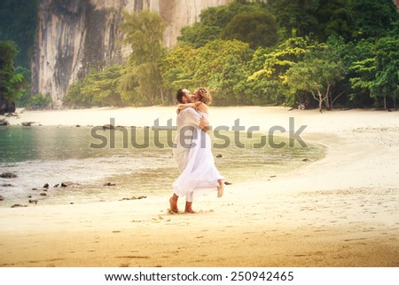 blonde bride and handsome groom whirl and kiss on sandy beach against green cliff and azure sea background - stock photo