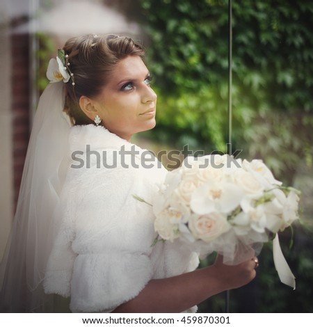 Blonde bride in fur coat holds a wedding bouquet standing outside
