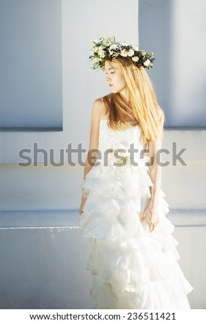 Blonde bride with white wreath standing against wall - stock photo