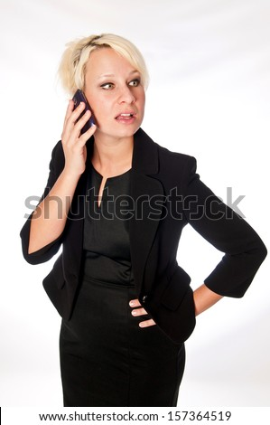 Blonde business woman on a mobile phone, looking camera right with a concerned look on her face. - stock photo