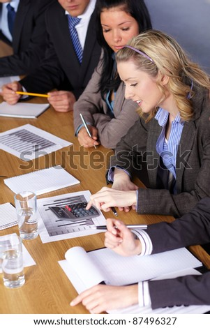 Blonde businesswoman and her team sits at conference table and work on some calculations - stock photo