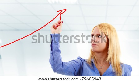 Blonde businesswoman drawing a growing business graph