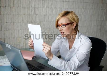 Blonde businesswoman got bad news, reading document - stock photo
