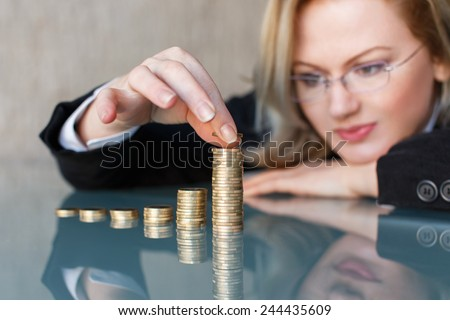 Blonde businesswoman in glasses building growing one euro columns, saving money concept. - stock photo