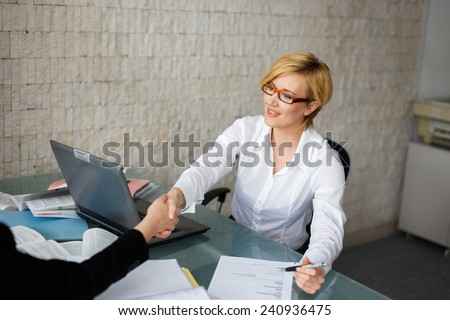 Blonde businesswoman in glasses handshake in office - stock photo