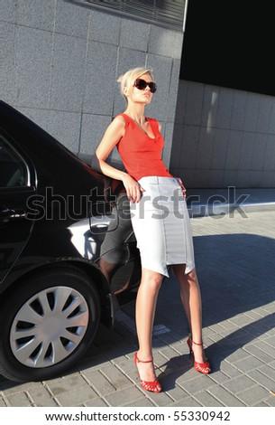 blonde businesswoman near black car in the city - stock photo