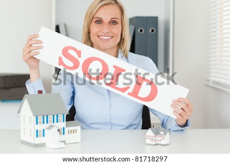 Blonde businesswoman showing SOLD sign looking into the camera in her office - stock photo