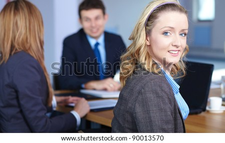 Blonde businesswoman sitting at conference table during business meeting - stock photo