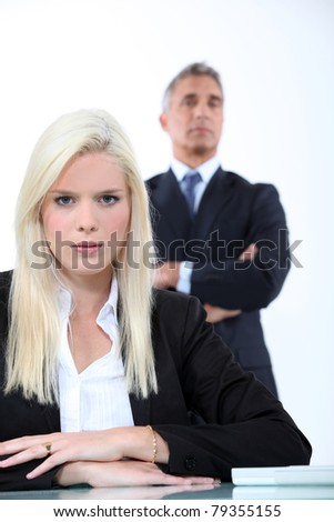 Blonde businesswoman sitting in front of her boss - stock photo