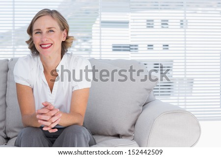 Blonde businesswoman sitting on couch during break time - stock photo